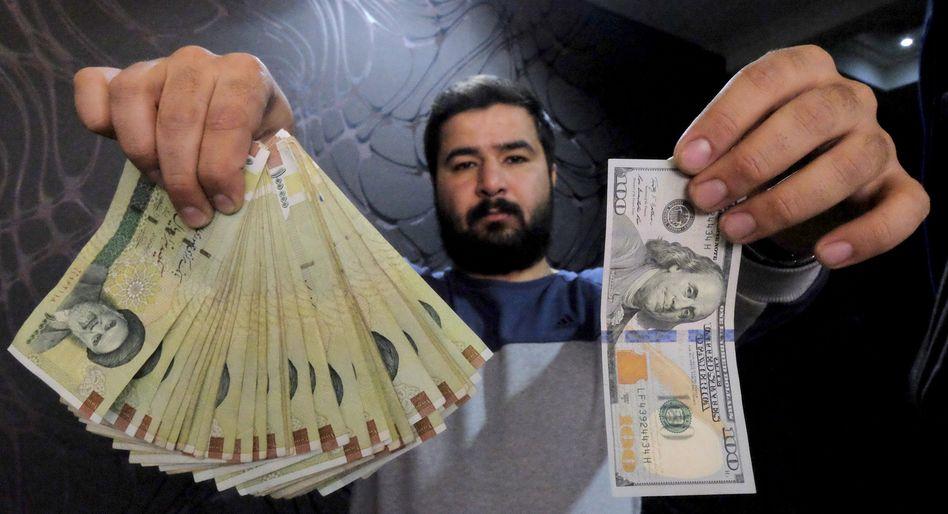 Iraner mit Geldscheinen: Der Rial befindet sich auf rasanter Talfahrt gegenüber dem US-Dollar.