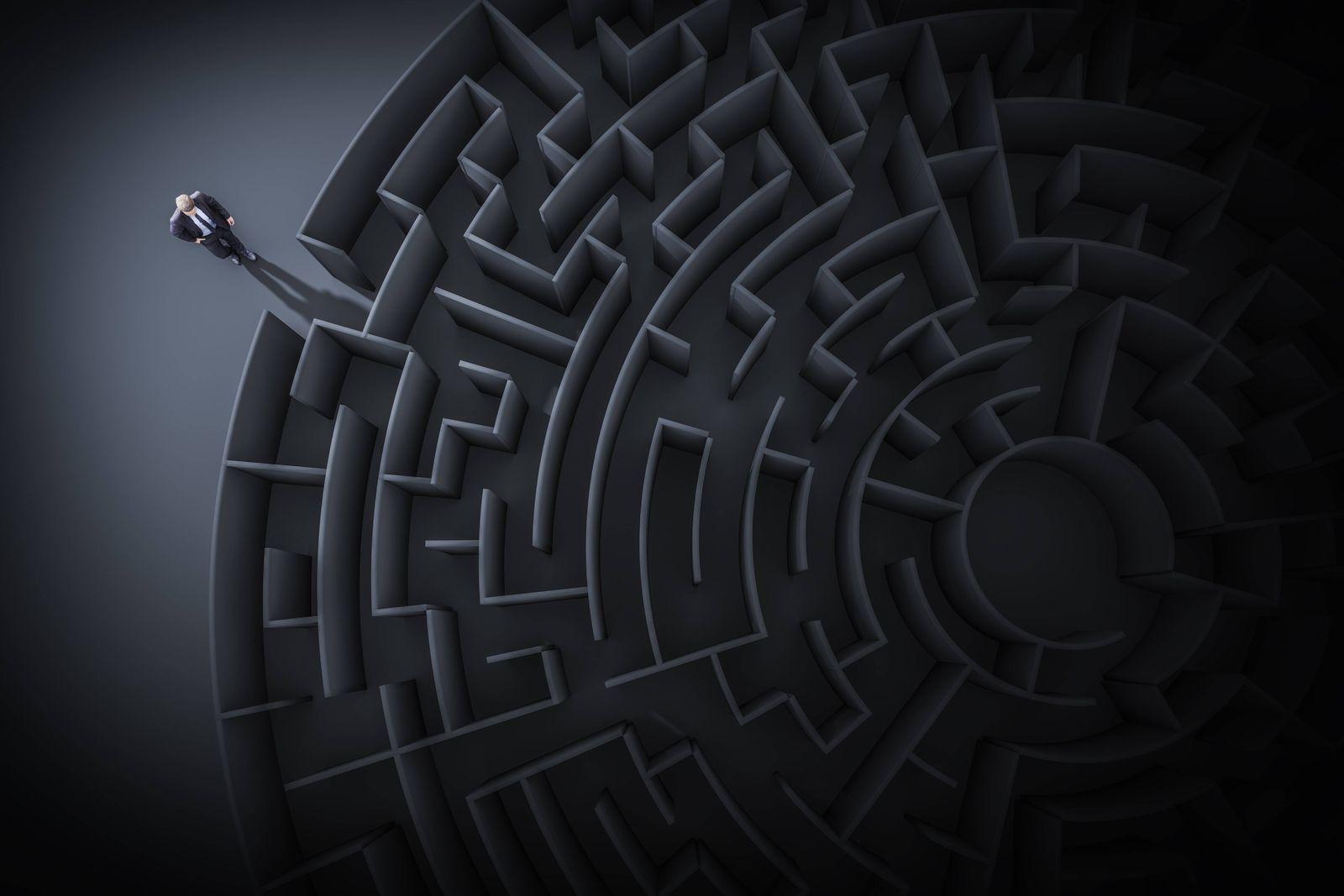 3D Computergrafik Geschaeftsmann steht am Eingang zu einem Labyrinth vor schwarzem Hintergrund 3D c