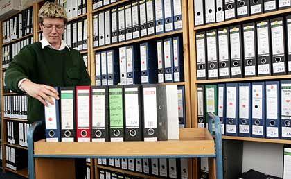 Aktenberge: Eine Justizbeamtin sortiert Falk-Ordner