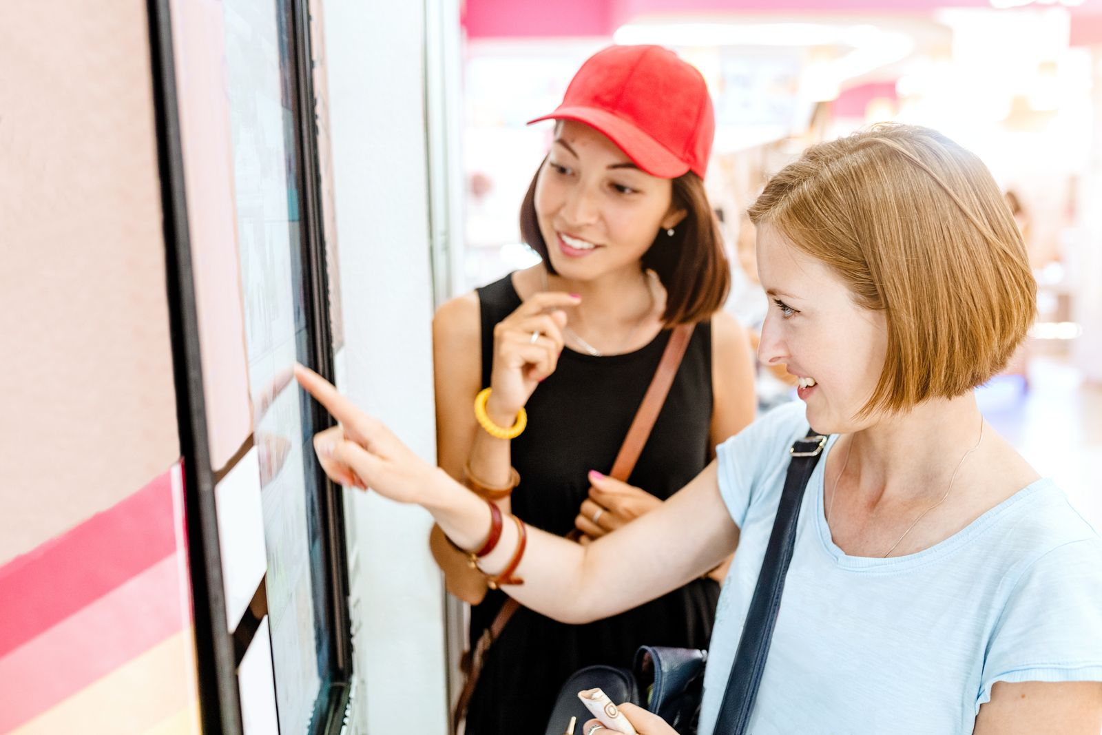 Two friends woman using automated self-service machine with big digital touch screen. Modern techmology concept