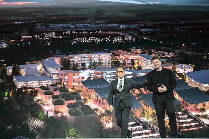 Toyota-Chef Akio Toyoda und Star-Architekt Bjarke Ingels vor einer Illustration der geplanten Prototypen-Stadt