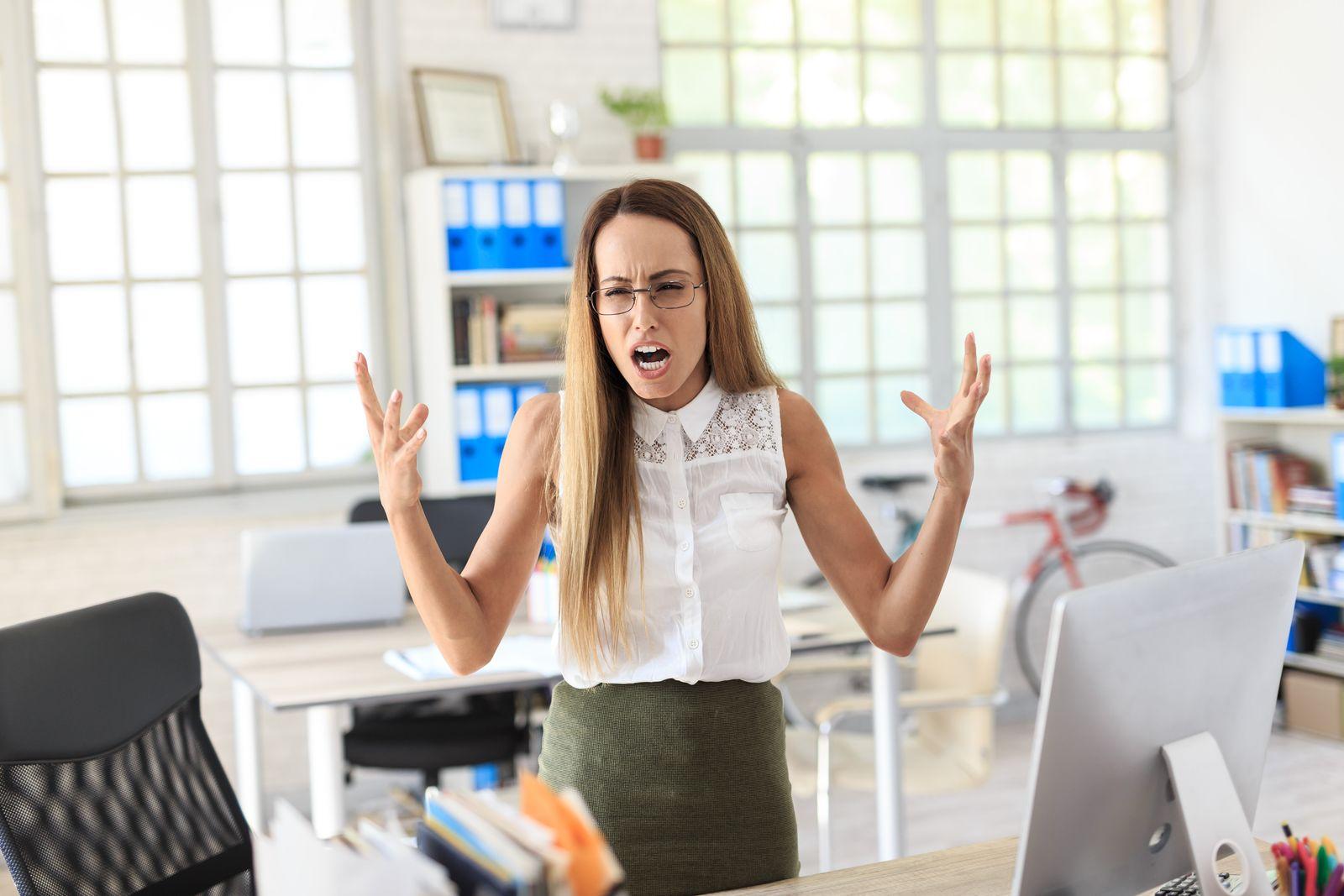 Furious businesswoman shouting at work