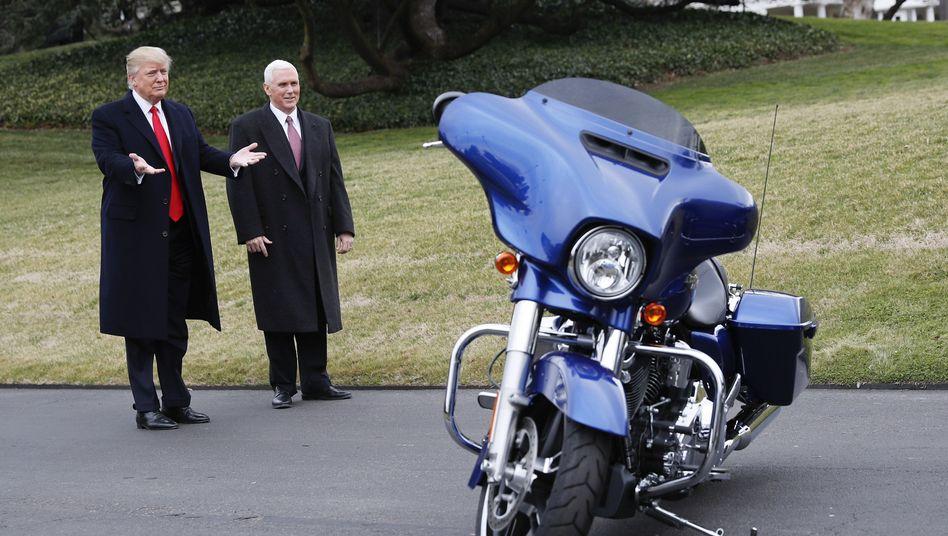 Erst bewundert, jetzt verdammt: US-Präsident Donald Trump (l.) und Vizepräsident Mike Pence bestaunen eine Harley Davidson, die neben dem Südrasen des Weißen Hauses in Washington geparkt ist. Manager des Konzerns hatten im Februar den Präsidenten besucht
