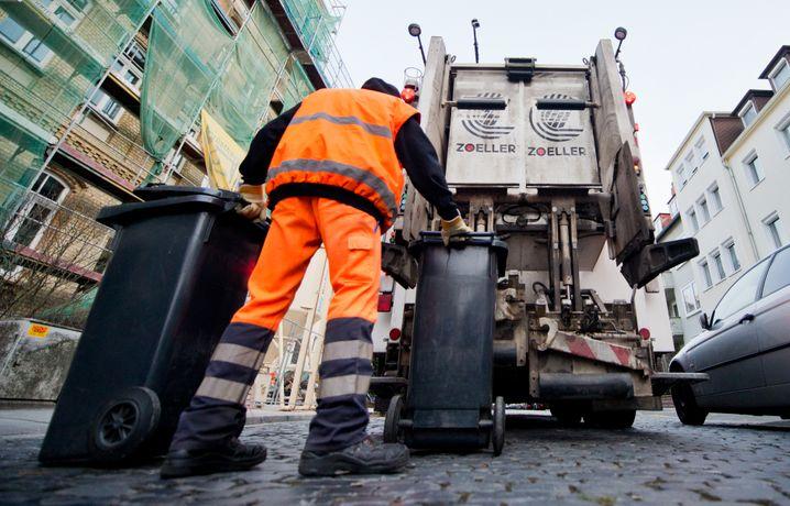 Hauptsache praktisch: Ein Mitarbeiter der Abfallwirtschaft bei der Arbeit in typischer Kleidung