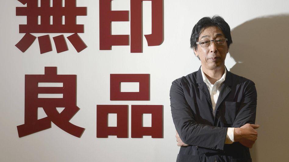 """Masaaki Kanai, Chairman von Ryohin Keikaku, vor dem Markenlogo """"Muji""""."""