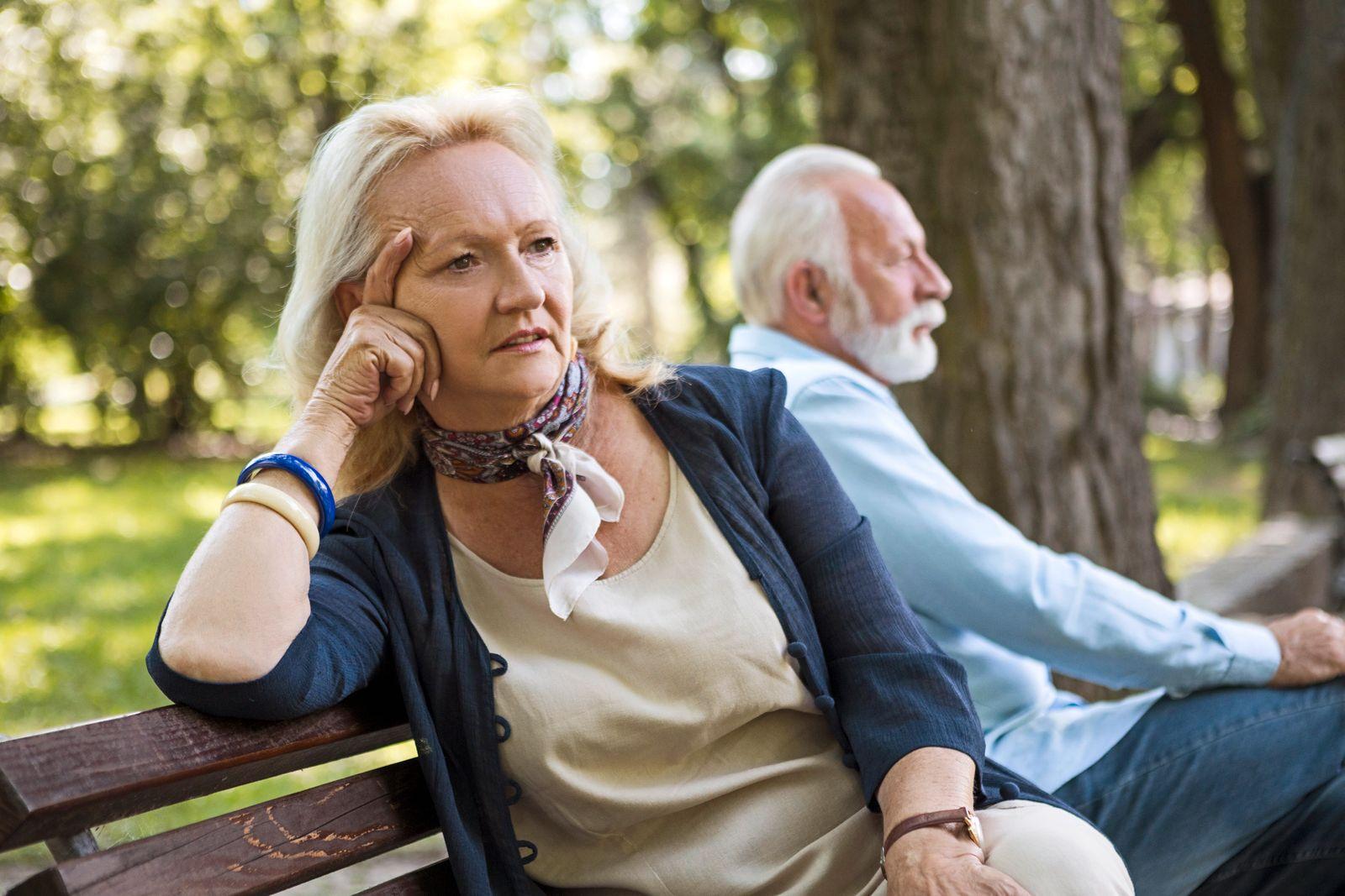 Depressed senior couple on a park bench