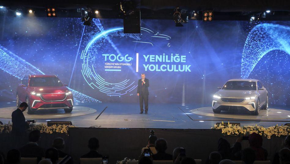 Recep Tayyip Erdogan zwischen den beiden präsentierten Togg-Modellen