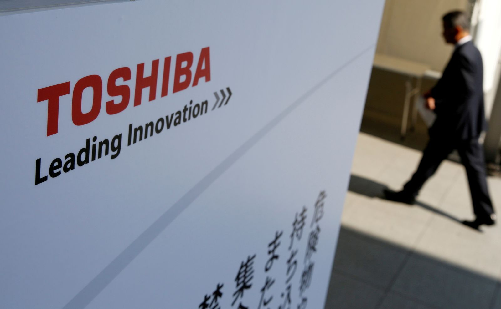FILE PHOTO: The logo of Toshiba is seen as a shareholder arrives at an extraordinary shareholders meeting in Chiba