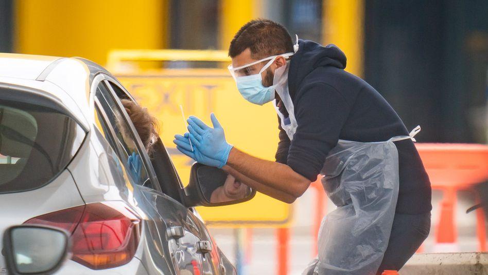 Ein Mitarbeiter des National Health Service (NHS) nimmt Speichelproben in London von Autofahrern in einer Einrichtung für Covid-19-Tests