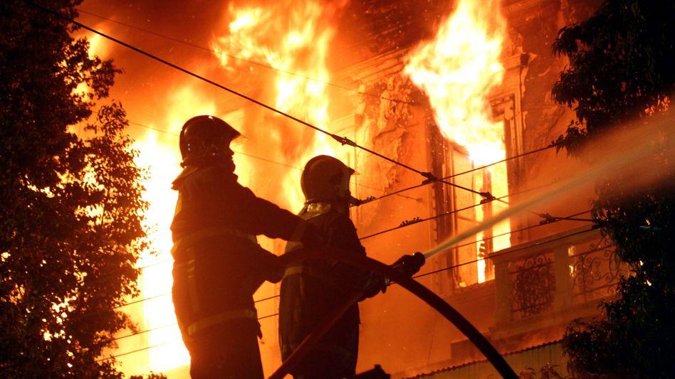 Löscharbeiten an brennendem Kino: Gewalttätige Demonstranten haben in Athen gegen die neuesten Sparbeschlüsse des griechischen Parlaments protestiert