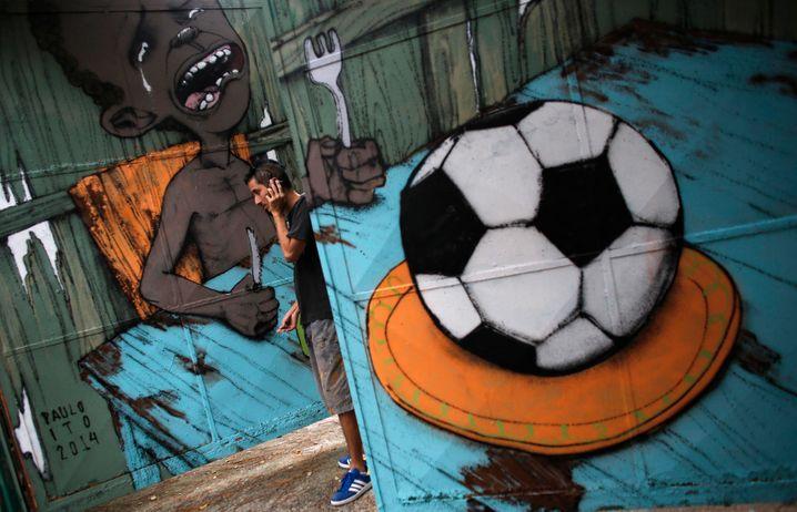 Kein Anschluss: Telefonierender Künstler vor WM-kritischem Graffito