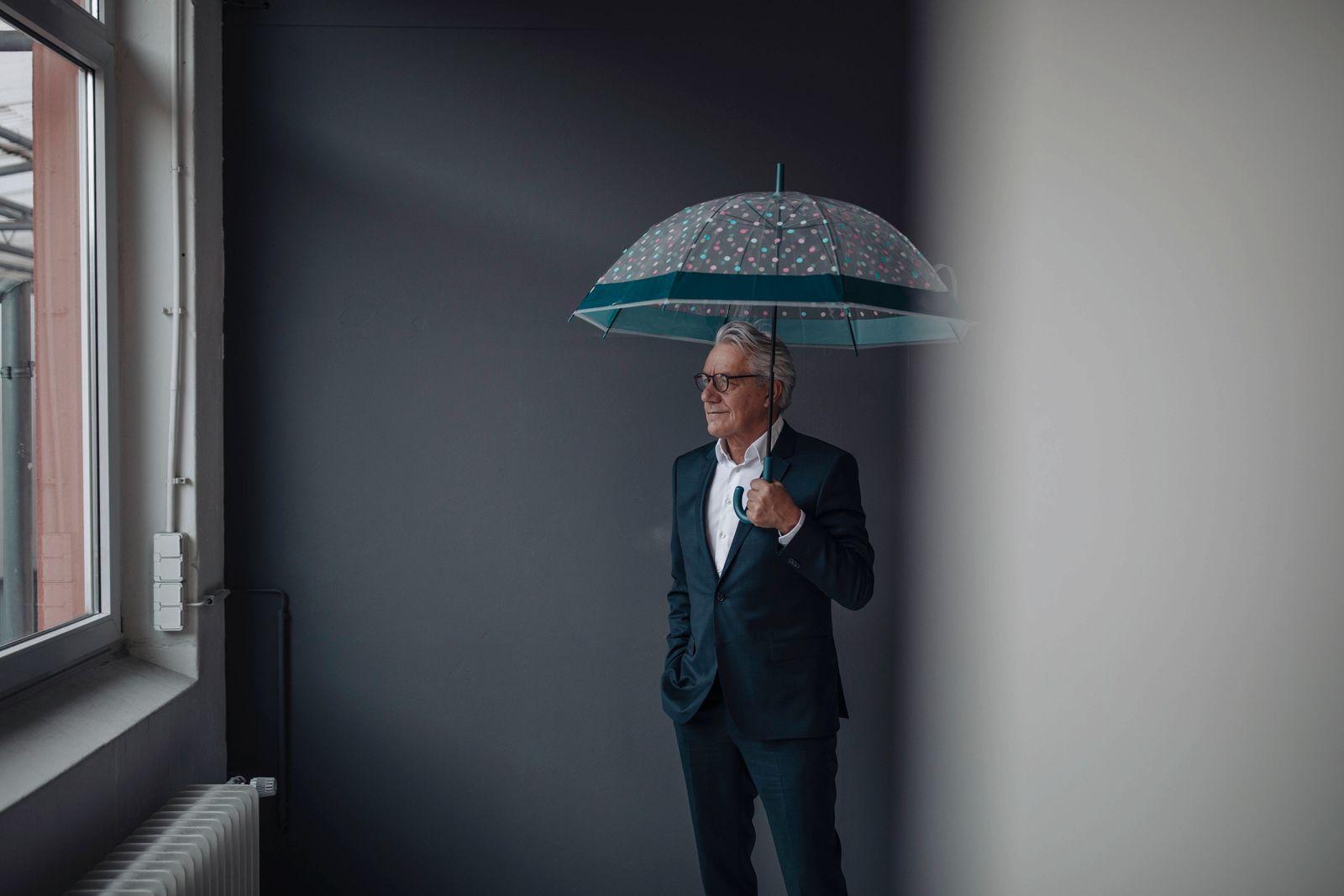 Senior businessman holding umbrella model released Symbolfoto property released PUBLICATIONxINxGERxSUIxAUTxHUNxONLY GUS