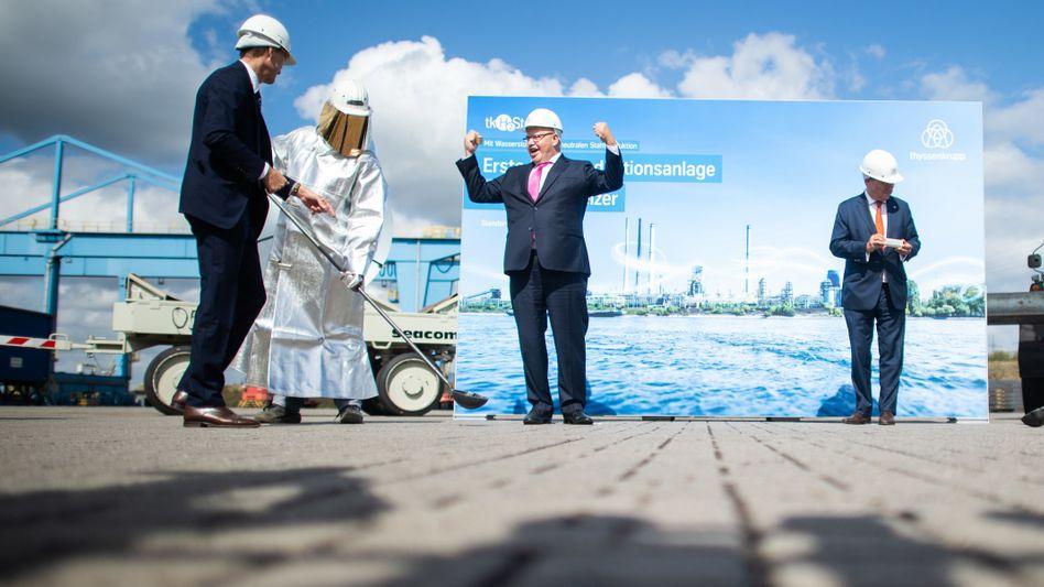 Bundeswirtschaftsminister Peter Altmaier (Bildmitte) posiert mit NRW-Regierungschef Armin Laschet (r.) und einer Mini-Stahlbramme aus dem neuen Produktionsverfahren.