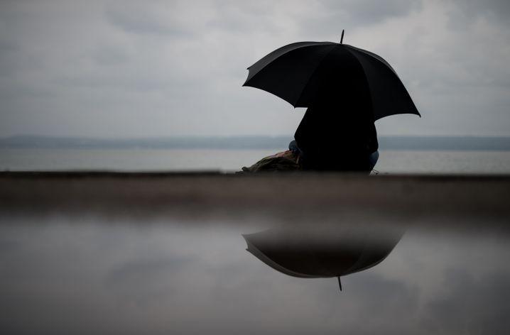 Auch Schirme können alt machen. Der dunkle Schatten im Inneren eines schwarzen Regenschirms betont vor allem Abwärtsfalten im Gesicht.