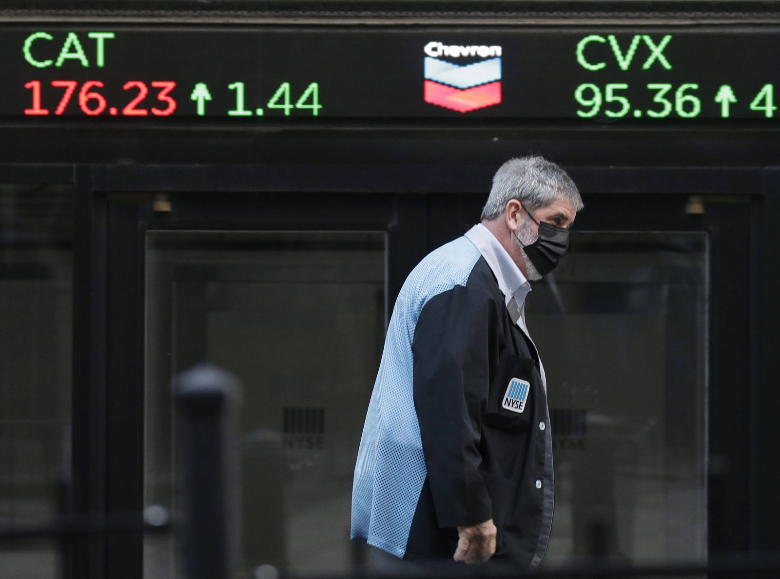 A trader walks by a ticker at the New York Stock Exchange before the closing Bell at the NYSE on Wall Street in New Yor
