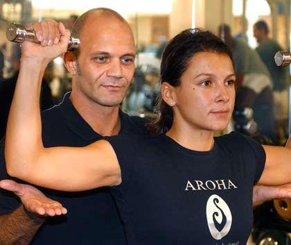 Beim Gewichteheben ist Vorsicht geboten: Der Trainer passt auf, dass die Kundin sich nicht verhebt