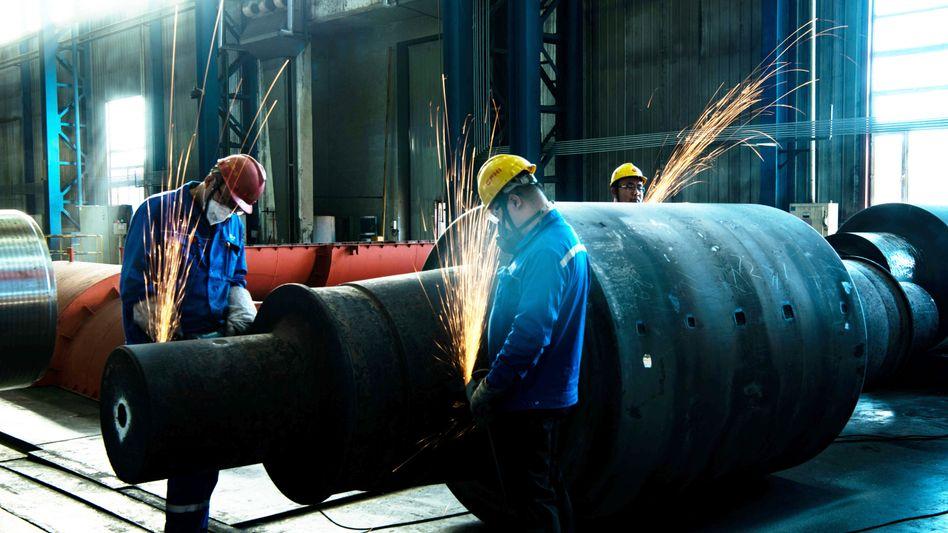 Chinesische Arbeiter schweißen in einer Fabrik für Maschinenbau