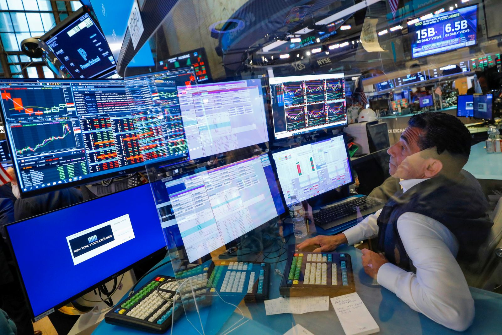 A trader works behind plexiglass on the floor of the New York Stock Exchange (NYSE) in New York City, New York