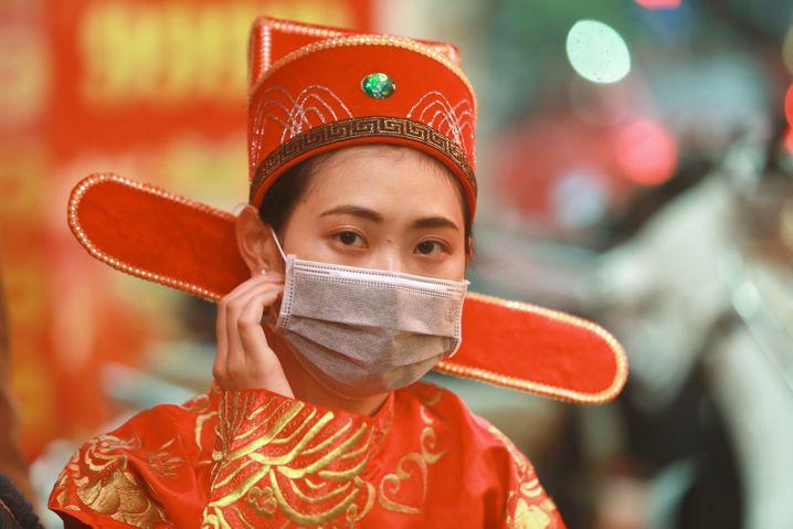 Menschen in Asien (hier eine Frau in Vietnam) sind auf öffentlichen Straßen kaum noch ohne Mundschutz anzutreffen. Das Coronavirus greift immer mehr um sich. In der besonders betroffenen chinesischen Provinz Hubei waren an einem Tag 14.840 neue Fälle registriert worden. Man fragt sich besorgt, ob die Behörden zuvor versucht haben, die Zahlen zu schönen.
