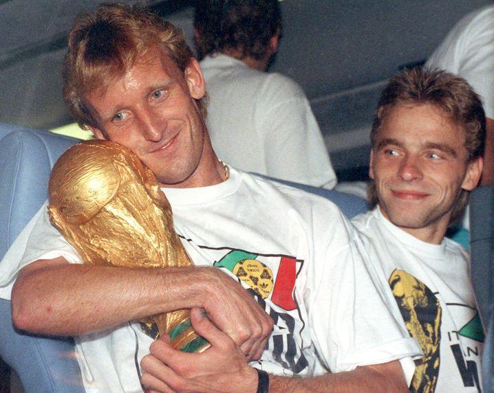 Andreas Brehme mit Thomas Häßler (rechts) und WM-Pokal