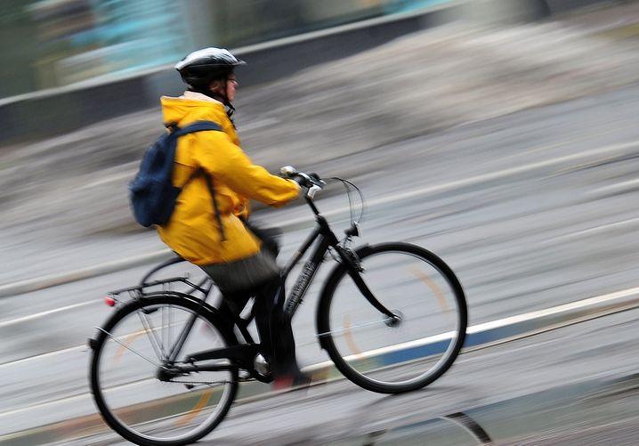 """ARCHIVâ - Eine Frau mit Fahrradhelm fâ°hrt bei Regen mit dem Fahrrad durch Berlin (Archivbild vom 14.01.2011). Eine neue Studie des Allgemeinen Deutschen Fahrrad-Clubs (ADFC) zeigt: Jeder zweite Radfahrer fÂ?hlt sich im Straï¬enverkehr nicht sicher, aber nur jeder achte trâ°gt konsequent einen Schutzhelm. Foto: Hannibal dpa/lbn (zum dpa-KORR: """"Mit mulmigem GefÂ?hl aufs Rad - und trotzdem ohne Helm"""" vom 01.12.2011) +++(c) dpa - Bildfunk+++"""