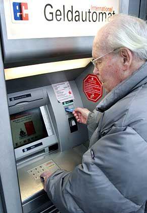 Bankkunde am Geldautomaten: Bislang bestritten Banken, dass es möglich sei, die Verschlüsselungscodes zu knacken.