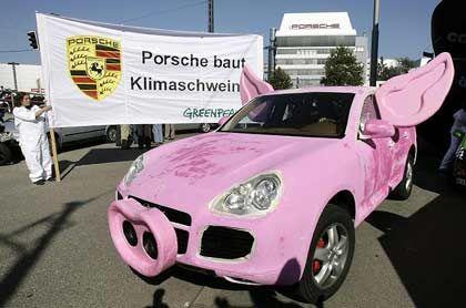 """""""Klimaschwein"""": Mit dieser Aktion fuhren Greenpeace-Aktivisten vor den Werkstoren von Porsche und BMW auf."""