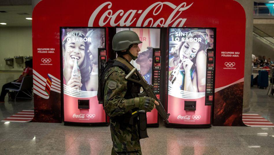 Coca-Cola-Werbung nebst Sicherheitspersonal in Rio de Janeiro: Der Getränkekonzern gehört seit Jahrzehnten zu den Unternehmen, die ihren Aktionären zuverlässig Dividenden überweisen