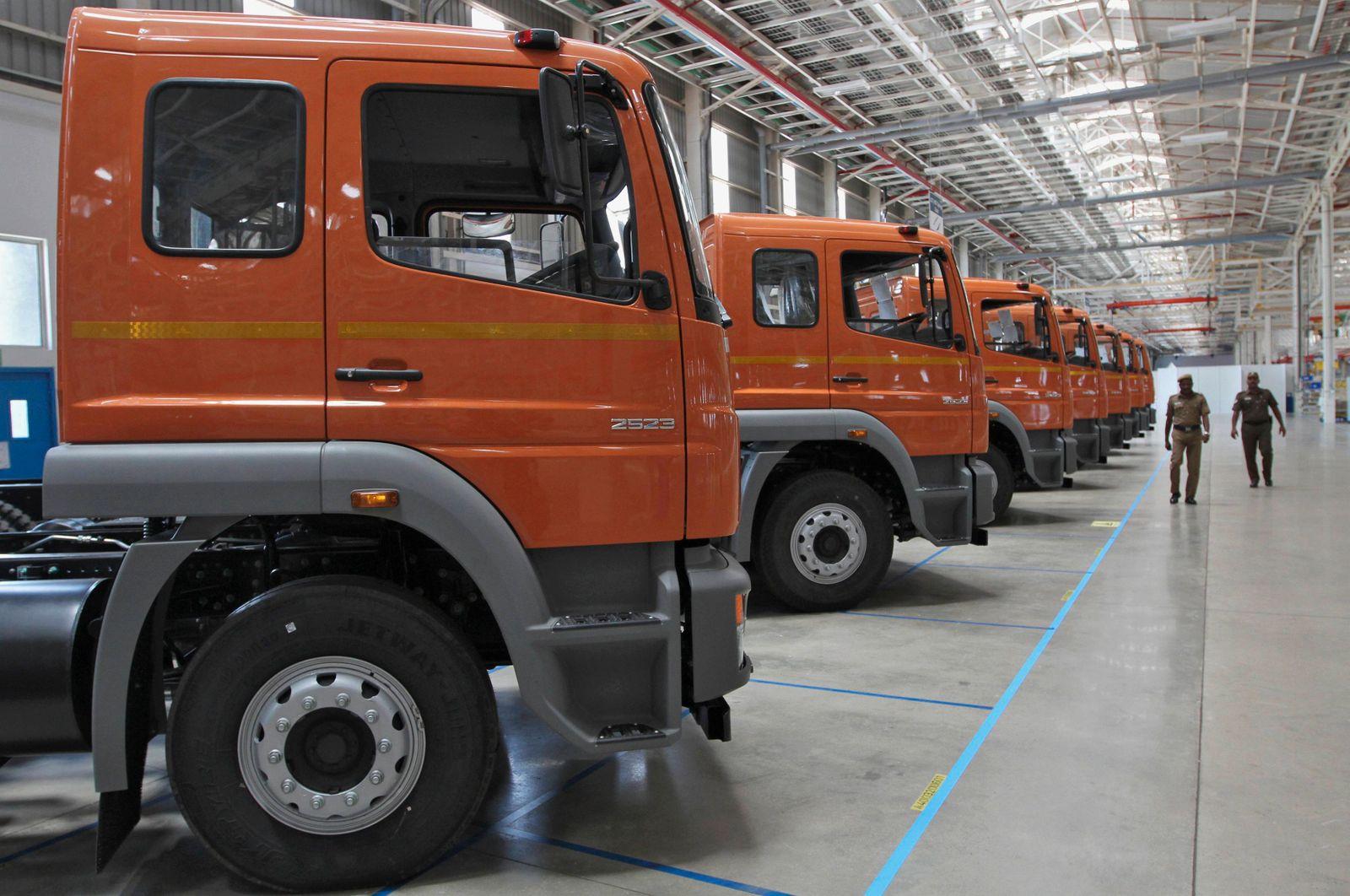 Policemen walk past a row of BharatBenz trucks inside Daimler's new factory in Oragadam