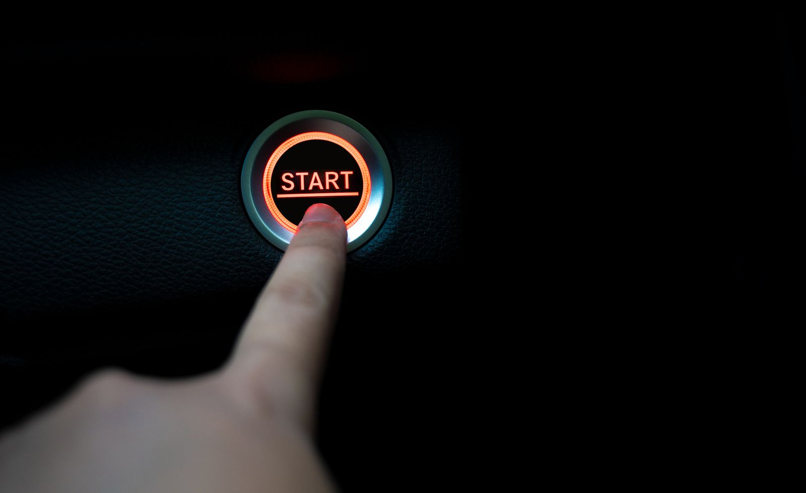 The fingers are pressing the start push button. Startup concept.