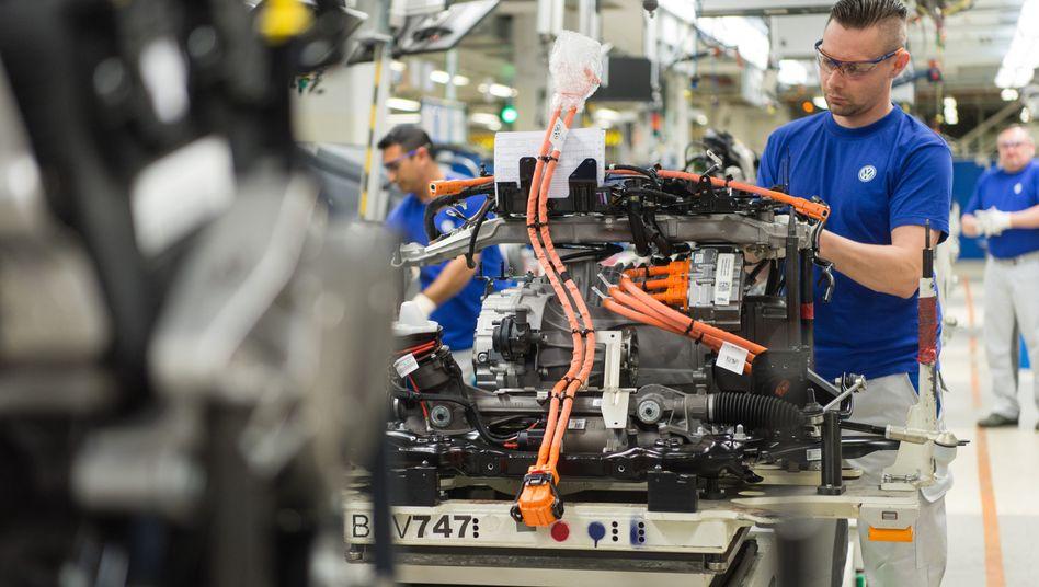 Ein VW-Mitarbeiter befestigt ein Bauteil am Motorblock für den Hybrid-Golf.