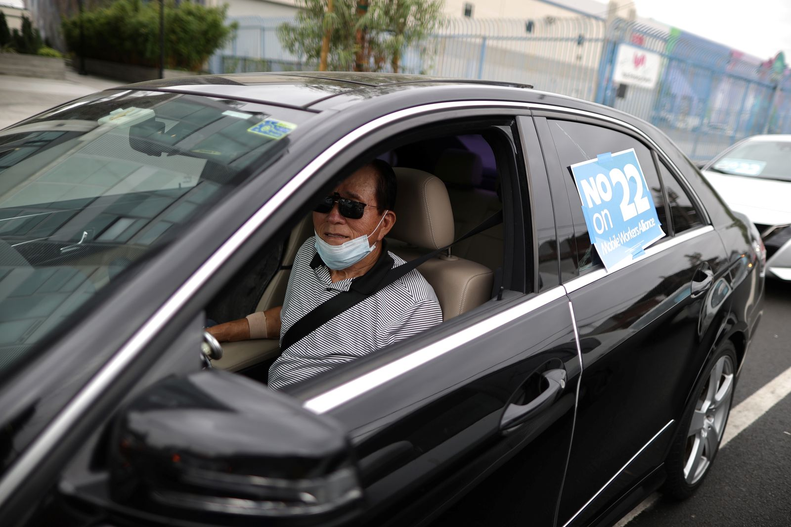 Rideshare driver Peter Hong, 67, joins a car caravan at a protest by Uber and Lyft drivers against the upcoming California Proposition 22 ballot measure, which would exempt rideshare companies from classifying their drivers as employees, in Los Angeles