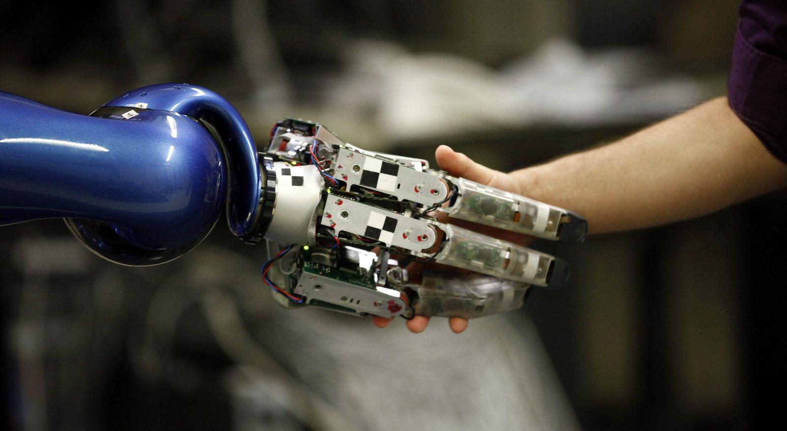 Roboterhand drückt Menschenhand