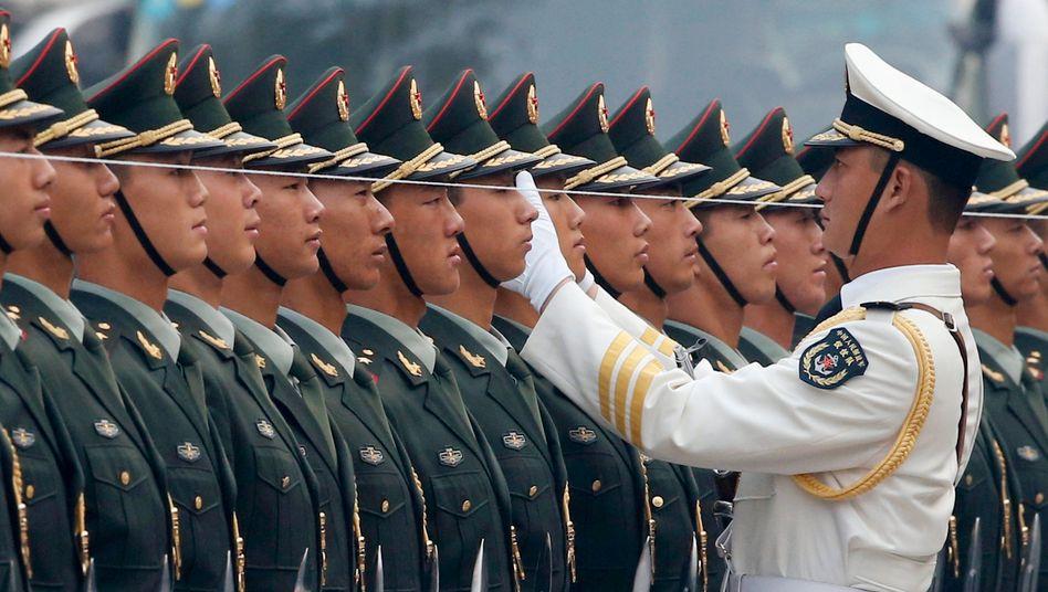 Ein Offizier der Volksbefreiungsarmee bringt seine Soldaten mithilfe einer Schnur in Reih und Glied.