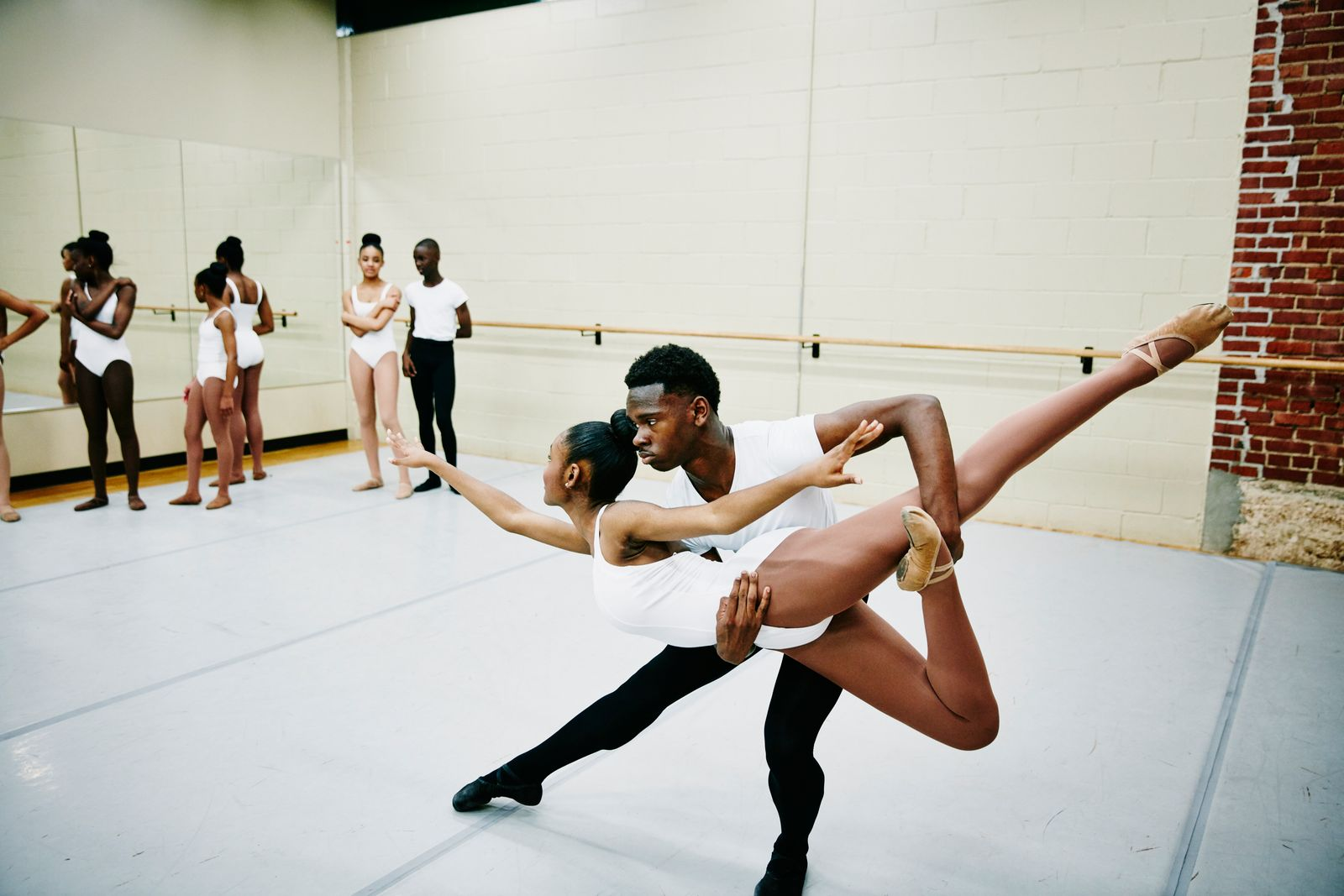 Ballet dancer lifting partner during rehearsal