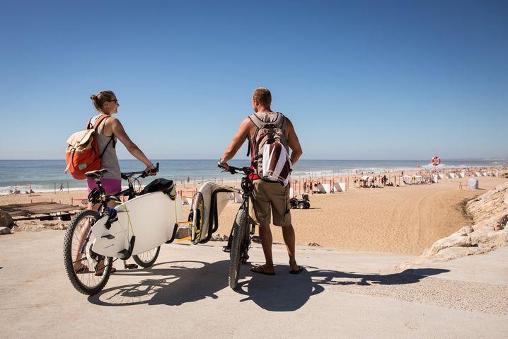 Surf-Mekka: Wellenreiter mit Rad am Strand Praia Grande in Portugal