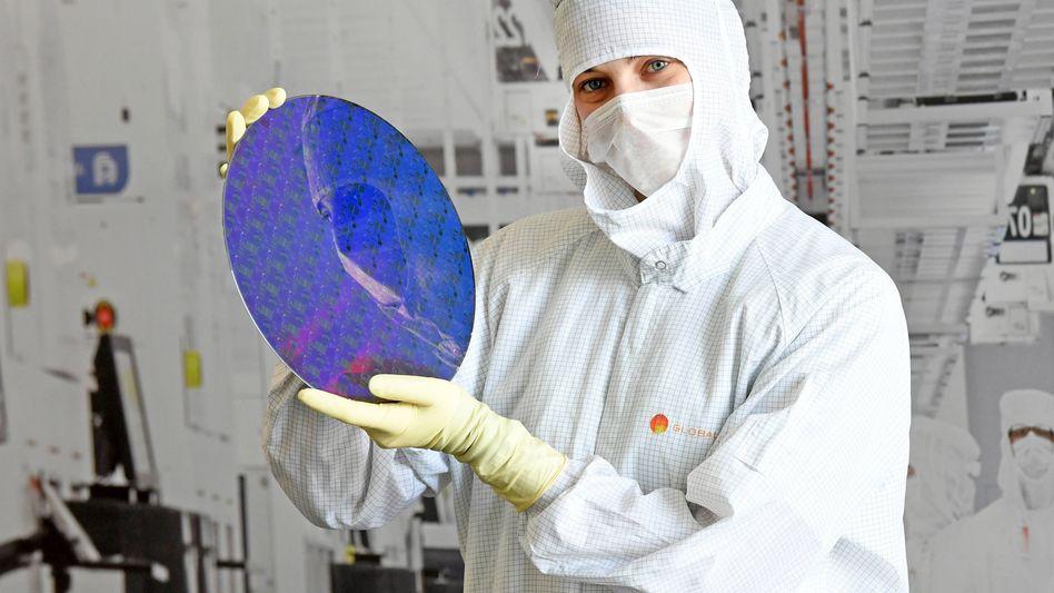 Davon kann die Autobranche aktuell nicht genug bekommen: Trainee in einer Chipfabrik von Global Foundries in Dresden mit einem Silizium-Wafer für die Halbleiterherstellung