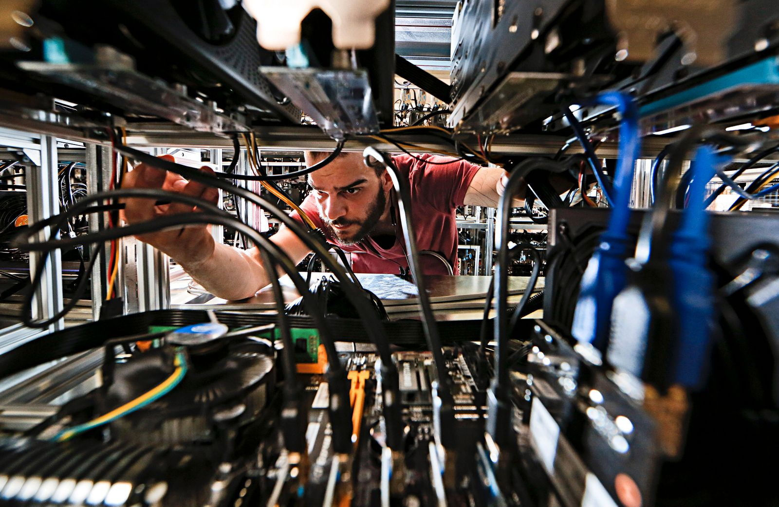 An employee works on bitcoin mining computers at Bitminer factory in Florence