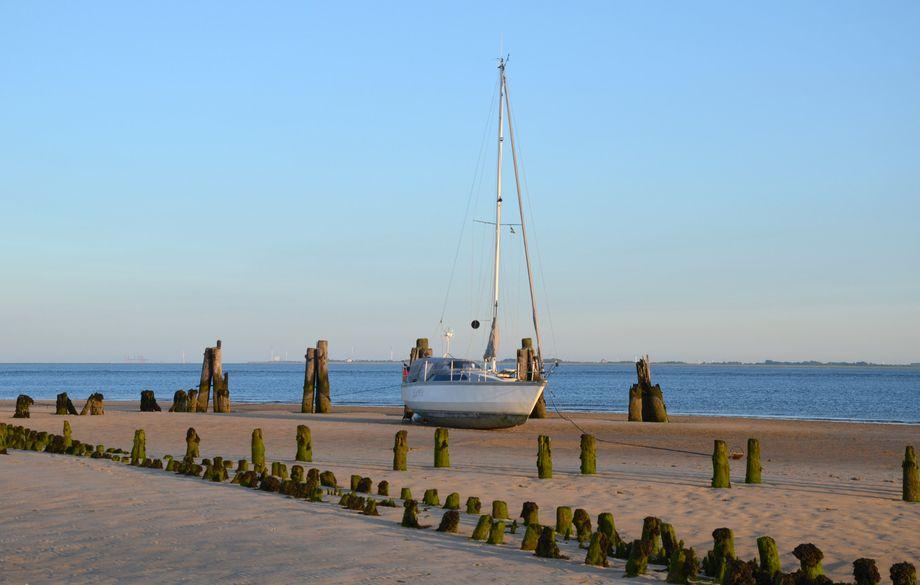 Das Wasser hat sich zurückgezogen: In Ostende auf Wangerooge liegt ein Boot bei Ebbe auf dem Wattboden