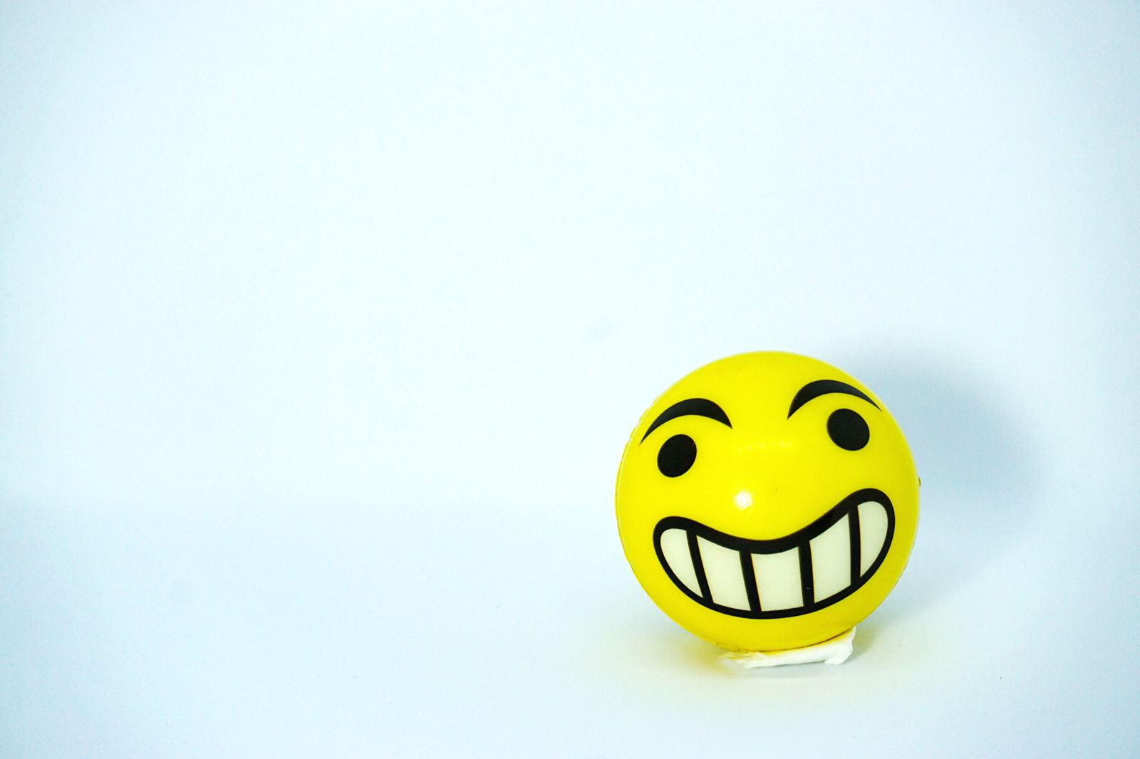 Smiley emoji yellow stress ball with white background. Happy and emoji concept.