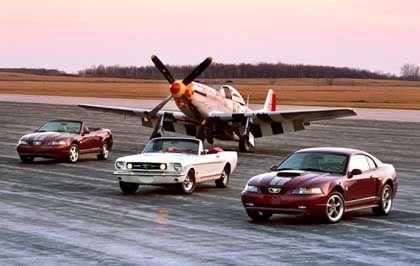 Mustang-Parade: Zwei Jubiläumsmodelle des Ford Mustang (r.u.l.) neben einem Mustang aus dem Jahr 1965 vor Oldtimerflugzeug P51 Mustang
