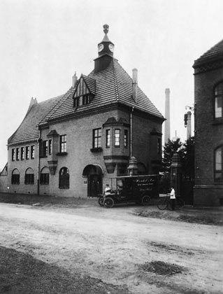 1948: Das Bürohaus Henkel in Holthausen mit dem ersten Werkstor und der Pförtnerloge