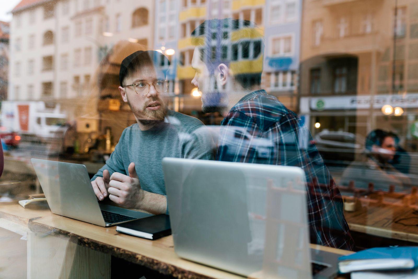 EINMALIGE VERWENDUNG Start-Up / Hipster arbeiten im Cafe