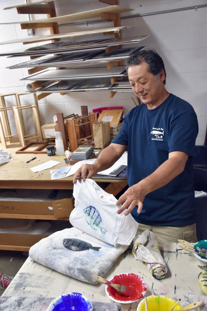 Naoki Hayashi zeigt eines seiner Werke, ein Fischdruck-T-Shirt