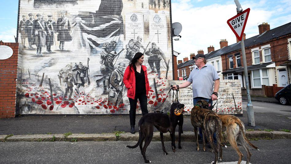 DUP-Abgeordnete Emma Little Pengelly vor Bürgerkriegsgemälde in Belfast