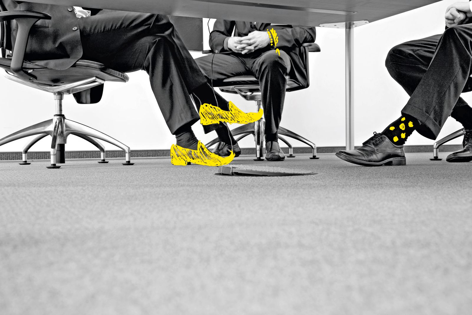 3 Beinpaare unter Konferenztisch