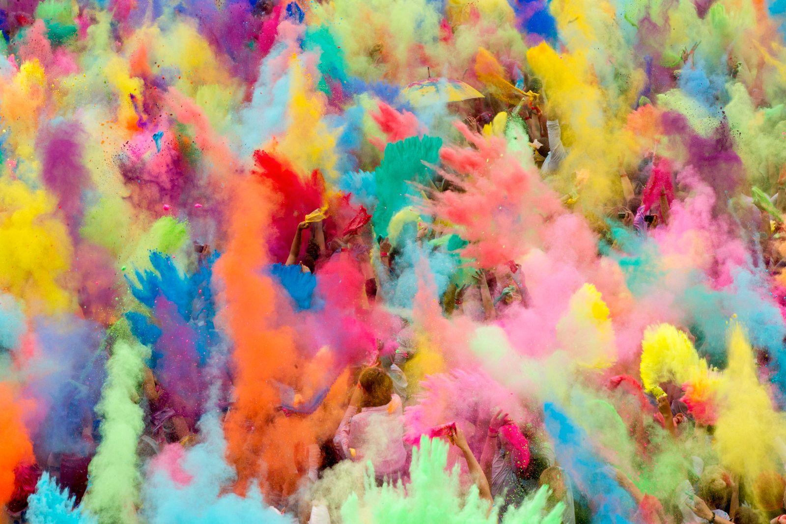 People throw coloured power in the air during Holi festival celebrations in Berlin