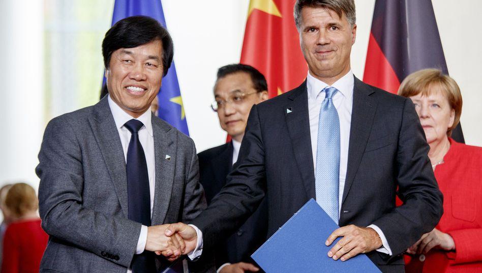 Da stapelten sie noch tief: Brilliance-CEO Qi Yumin und BMW-Chef Harald Krüger am Montag nach der Unterzeichnung eines Kooperationsabkommens in Berlin.