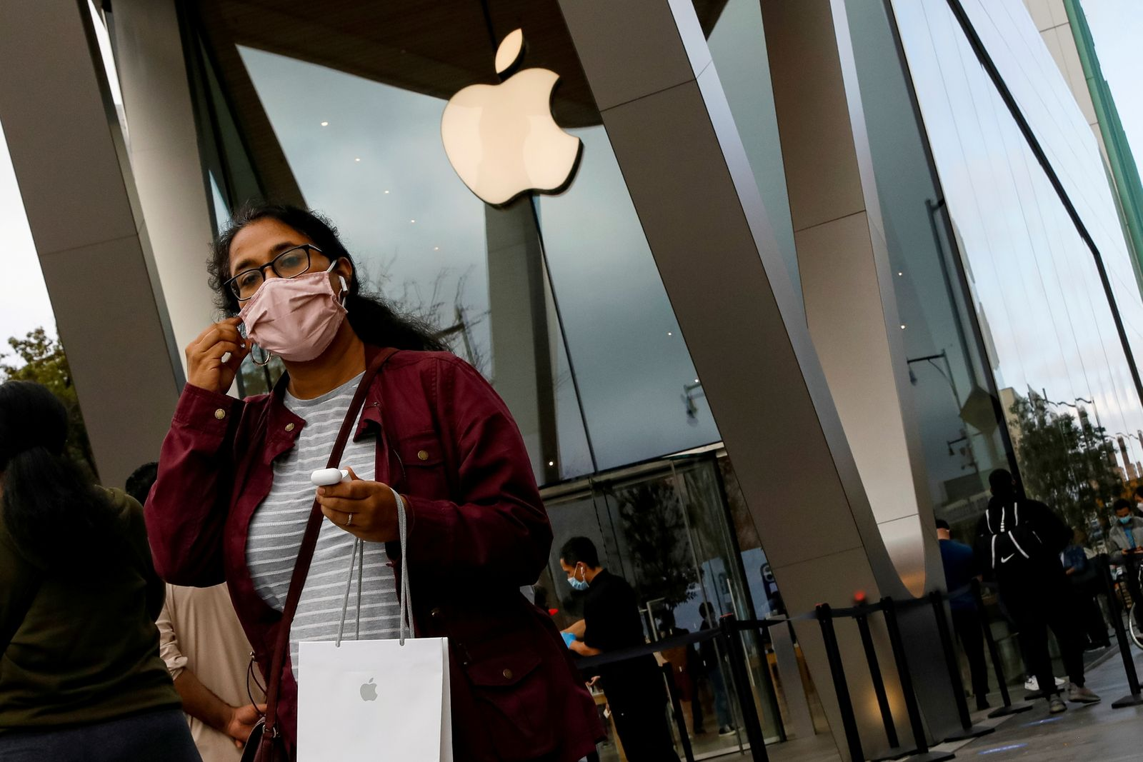 FILE PHOTO: A customer exits after picking up Apple's new 5G iPhone 12 that went on sale at an Apple Store in Brooklyn, New York