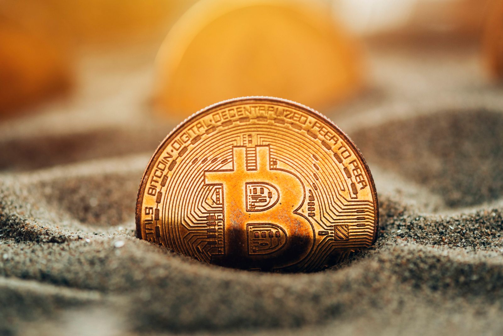 Cryptocurrency mining, conceptual image Bitcoin cryptocurrency coins buried in sand. Conceptual image for crypto mining